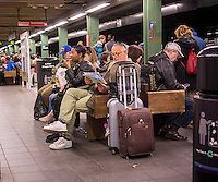 Travelers wait for their trains in the Times Square station in the New York subway on Sunday, April 26, 2015. (© Richard B. Levine)