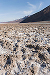 Death Valley National Park, California;  a view of the salt crust and underlying mud formations which have formed from repeated freeze–thaw and evaporation cycles on the floor of Badwater Basin, in early morning sunlight, Badwater is the lowest point in North America at 282 feet below sea level