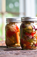 Glass bottles of pickled vegetables in the sunshine.