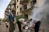 Men grill meat outside a destroyed apartment block in preparation for Valter Mirzoyan's 50th birthday party in Shushi, Nagorno-Karabakh.