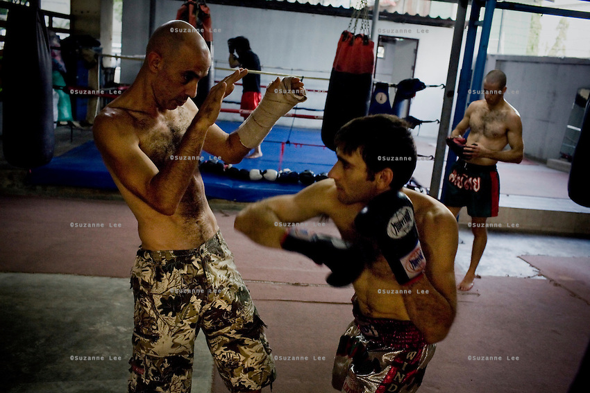 """Shuki (left) coaches Gili (2nd from right) as Eran (right) takes a break in Rompo Muay Thai Gym, Khlong Toei, Bangkok city, Thailand on 14th December 2009..Shuki Rosenzweig, aged 40, is a professional Muay Thai Boxing fighter (champion) and trainer who has lived for 9 years in Thailand. He is famous in Israel as the authority of this sport. Started at the age of 12 in boxing in Israel, Jerusalem. Used to work in the fish market. His father is a 'legend' in Jerusalem fish market. Shuki stopped working with his dad about 13 years ago. He has opened some muay thai gyms in Thailand in the past. He currently has about 5 Israeli fighters under his training in Bangkok, besides fighters of other nationalities. Shuki found religion in Bangkok with Chabad about 4 years ago. He never misses Shabbat and loves to sing the songs of prayer, priding himself with a good voice. """"Chabad integrates all Jews. it keeps us together. When at Chabad, we are at home, united with people of the same culture, language and beliefs""""..Gil Saat (known affectionately as Gili), aged 29, from Ramat Gan, Israel, has been a boxer for 9 years. He is on his second trip to Thailand for muay thai. On the first trip, he stayed for 6 months, fighting in about 10 competitions in Thailand and once in Cambodia. Gili has graduated in many sport related courses from institutes in Thailand and Israel, including a diploma in Thai massage. He first met Shuki in Israel many years ago at a competition when Shuki was the trainer for Gili's opponent in the ring. A few years after that, Gili attended a seminar given by Shuki about muay thai and then decided to come to Thailand to train under him. Gili comes from a more religious family in comparison to Shuki. Gili's grand father is a rabbi in Israel. Gili introduced Shuki to Chabad (both Khao San and Sukhumvit) about 4-5 years ago and they have since spent every shabbat at Chabad. On 4th Dec 2009, they both turned up for shabbat immediately after a competition, still blee"""