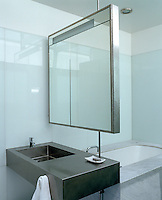 A narrow bathroom cabinet also serves as a screen separating the bath from the stainless steel wash basin