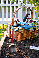 A basket of garden tools, seeds and gloves sits on the soil of a raised planter, ready for the gardener.