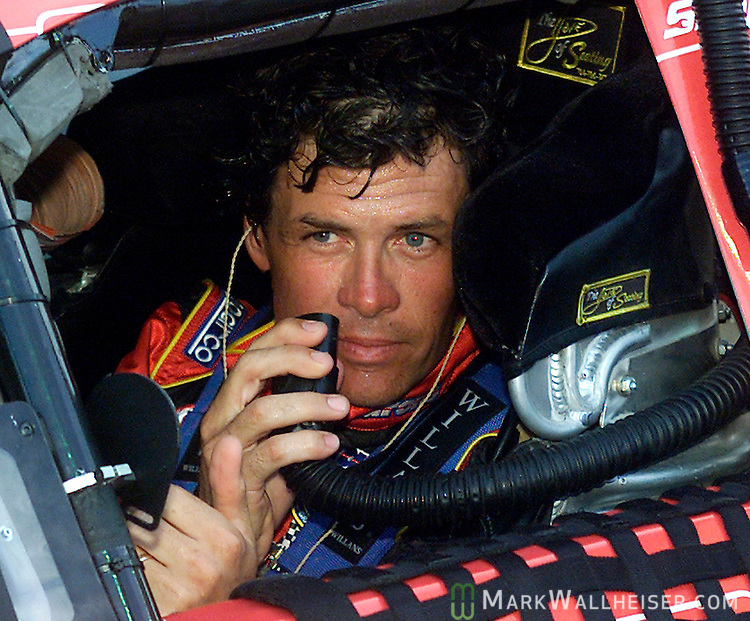 Michael Waltrip holds an air conditioning hose in his number 99 Aaron's/Terminator Chevrolet on pit road before starting in the Winn Dixie 250 Busch Series race at the Daytona International Speedway in Daytona Beach, Florida July 4, 2003.