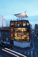The eco-house designed by Pablo Katz glows against the clear sky of a summer's evening in Paris