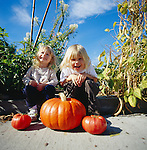 Two girls with a pumpkin and heirloom tomatoes at a vegetable garden in Seattle, WA