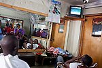 Men in a barber shop watch Spain play the Netherlands in the World Cup final on July 11, 2010 in Port-au-Prince, Haiti.