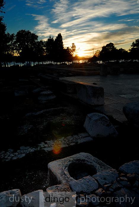 Sun setting over excavated Roman ruins, with lens-flare. Zadar, Croatia