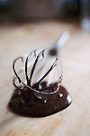 A whisk with chocolate dripping off on a wooden kitchen counter.