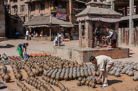 Bhaktapur, Nepal.  Potters at Work in Potters' Square.  Worshiper Making Offering at Shrine.  A Pati, a Neighborhood Shelter or Social Meeting Place in background.