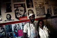 A Cuban bakery employees stand in front of a wall covered by pictures of the revolutionary leader Che Guevara, Alamar (the Eastern Havana), Cuba, 12 February 2009. During the Cuban Revolution, an armed rebellion at the end of the 1950s in Cuba, most of the revolutionary leaders started as no-name soldiers fighting in the jungle. Although the revolutionary leaders, after taking over the power, became autocratic rulers holding almost absolute power and putting the opposition in jail, for some reason Cuban people have never stopped to worship Fidel Castro, Che Guevara, Raul Castro and others. Cubans hang their photos and portraits on the wall in homes, shops and working places even they don't have to. The people of Cuba love their heroes.