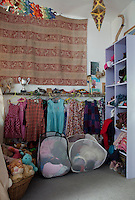 A storage solution in a child's bedroom with open shelving and baskets