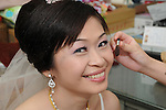 Taiwanese Wedding -- The lovely bride gets the final touches on her make-up before being led to greet the guests at the banquet.