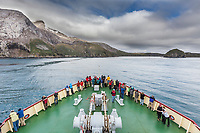 Tourists on the bow of the M/V Polar Star near the headland cliffs along the western shore of South Georgia Island.