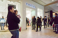 Last minute shoppers pass the Pandora jewelry store in the Queens Center Mall in the borough of Queens in New York on Christmas Eve, Saturday, December 24, 2016. A study reports that the holiday shopping season, November and December, now accounts for less than 21 percent of physical stores' sales, down from its peak of 25 percent. (© Richard B. Levine)