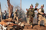 U.S. Army soldiers and Iraqi policemen pass two bodies as they seal off the scene of a massive October 27,2003  car bomb attack on the headquarters of the International Committee of the Red Cross (ICRC) in Baghdad, Iraq.