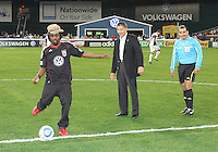 Will Chang owner of D.C. United watches hip-hop artist Wale kick out the ball during an MLS match against the New England Revolution on April 3 2010, at RFK Stadium in Washington D.C.