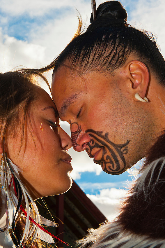 A Maori man with ta moko (facial tattoo) and woman doing hongi (traditional Maori greeting), Te Puia (New Zealand Maori Arts & Crafts Institute), Rotorua, New Zealand