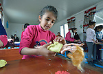 """A girl creates clothing for Barbie with modeling clay in a church-sponsored """"child-friendly space"""" in the village of Bakhtme, Iraq, which was flooded with displaced families when the Islamic State group took over nearby portions of the Nineveh Plains in 2014. The space is sponsored by the Christian Aid Program Nohadra - Iraq (CAPNI). It includes some children from the host community as well."""