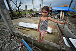 Precious Morta, 4, stands in the ruins of what was once her home in Tanauan, a city in the Philippines province of Leyte that was hit hard by Typhoon Haiyan in November 2013. The storm was known locally as Yolanda. Hundreds of families here have received water filters from the United Methodist Committee on Relief, a member of the ACT Alliance. UMCOR is also working with city officials to help residents here build permanent houses to replace those they lost in the storm.