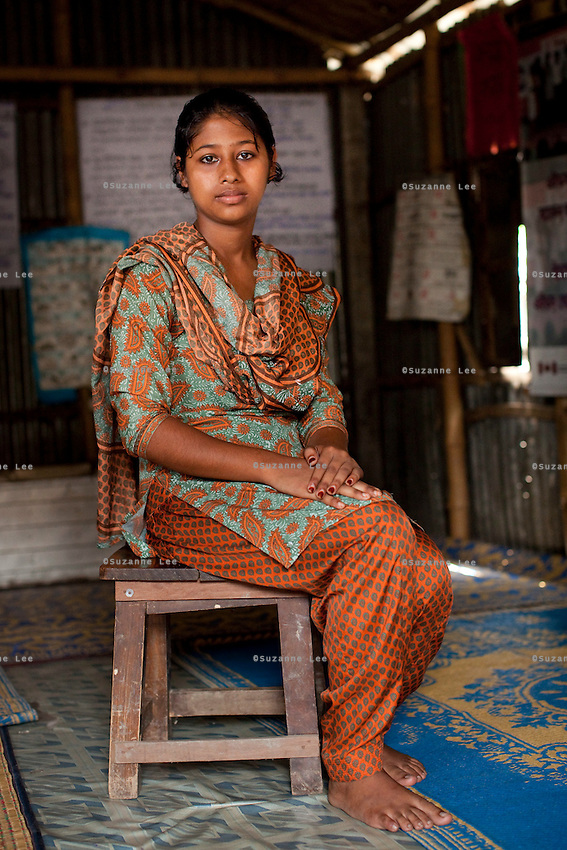"Nusrat Jahan Popy (16) sits for a portrait in the meeting hut of a Children's Group in Bhashantek Basti (Slum) in Zon H, Dhaka, Bangladesh on 23rd September 2011. Popy says, ""I feel helpless, not angry (if my parents would try to marry me off). I can do stitching and we want to be allowed to work so that we can earn money to support ourselves in our studies and to rid ourselves of poverty and gain independence."" The Bhashantek Basti Childrens Group is run by children for children with the facilitation of PLAN Bangladesh and other partner NGOs. Slum children from ages 8 to 17 run the group within their own communities to protect vulnerable children from child related issues such as child marriage. Photo by Suzanne Lee for The Guardian"