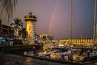 Fine Art Print Photograph in Puerto Vallarta Mexico of a rainbow over the yachts in the local marina. The Iconic Light-tower frames the background of this scene.