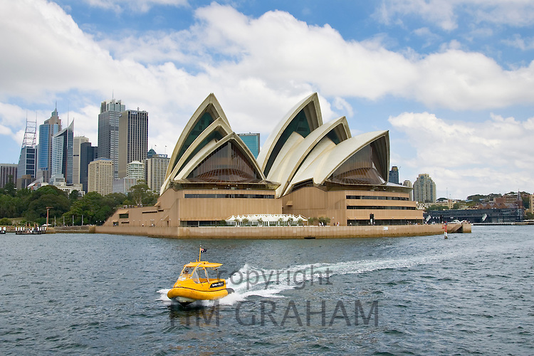 Speedboat passes Sydney Opera House in Sydney Harbour, Australia