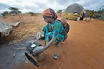 Ahada Kusoco Hassan, 23, cooks breakfast for her family in the Dadaab refugee camp in northeastern Kenya. Tens of thousands of newly arrived Somalis who have swelled the population of what was already the world's largest refugee camp.