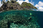 Split level coral reef and island with diver. Misool, Raja Ampat, West Papua, Indonesia,  January 2010