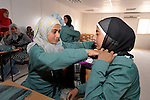 Girl students help each other try on new uniforms in the Zaatari Refugee Camp, located near Mafraq, Jordan. Opened in July, 2012, the camp holds upwards of 50,000 refugees from the civil war inside Syria. International Orthodox Christian Charities, which provided the uniforms, and other members of the ACT Alliance are active in the camp providing essential items and services.