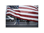 "Members of the Patriot Guard set up a flag outside the funeral of a member of the U.S. Army killed in Iraq. The Patriot Guard is a motorcycle group formed to provide escort and protection for the families of fallen service members. Washington, North Carolina, 2008 | Jeremy M. Lange | $350 | Limited Edition 2 of 7 | Print - 20x24"" Light Jet Fuji Crystal Archive, lustre 