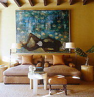 Comfortable chaise longues are flanked by a pair of leather drum side tables in this living area