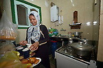 Mona Ahmed, a refugee from the Darfur region of Sudan, prepares tea in the kitchen of her family's crowded apartment in Cairo, Egypt. She and her husband have both taken adult education classes provided by St. Andrew's Refugee Services, which is supported by Church World Service.