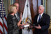 United States Vice President Mike Pence, right, swears in Betsy DeVos as U.S. secretary of education, with her husband Dick DeVos Jr. in the Vice President's Ceremonial Office in Washington, D.C., U.S., on Tuesday, Feb. 7, 2017. DeVos squeaked through a history-making Senate confirmation vote to become U.S. education secretary, as Vice President Mike Pence broke a 50-50 tie and Republicans staved off last-minute defections that would have killed her nomination. <br /> Credit: Andrew Harrer / Pool via CNP