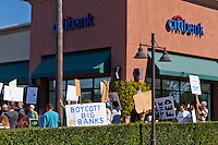 "Protesters hold signs in front of a Citibank in Irvine, CA during the Occupy Orange County, Irvine march on Saturday November 5.  A large ""Boycott Big Banks"" sign is visible."