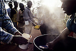 MYAGA, RWANDA - FEBRUARY 19: Prisoners accused of Genocide get breakfast in a solidarity camp February 19, 2003 in a rural area close to Myaga, Rwanda. 800,000 mainly Tutsis and moderate Hutus were killed in about one hundred days in Rwanda in 1994. About 100,000 prisoners accused of the genocide are still in prisons nine years later awaiting trials. Rwanda is currently trying to cope with these problems of crime, punishment and reconciliation through village trials called Gacacas. Gacaca, which means on the grass, is a traditional way of solving disputes between local communities and involve juries of residents. 11,000 gacacas are currently trying to resolve crimes from the genocide. (Photo by Per-Anders Pettersson)