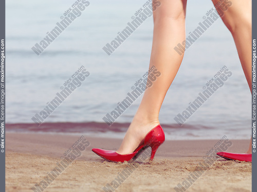 Inappropriately dressed for the situation, young woman walking on the beach wearing red  sexy high heel shoes