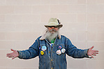 "Merrick, New York, USA. October 23, 2016. FRED S. CHANDLER, 66, of North Bellmore, wearing political campaign buttons supporting Democratic presidential candidate Hillary Clinton, holds his arms out wide to each side, as he attends rally to demand public water and stop New York American Water (NYAW) rate hike. On denim jacket were buttons for Hofstra University DEBATE 2016 - and ""So My Daughter Knows She Can Be President. Hillary 16"" - ""TRUMPBUSTERS"" - ""CLINTON KAINE 16"" - and Monopoly Man character with ""NEVER TRUMP"" text."