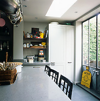 The kitchen has white units and grey work surfaces. There is plenty of room for a dining table and chairs in the centre of the sunny room