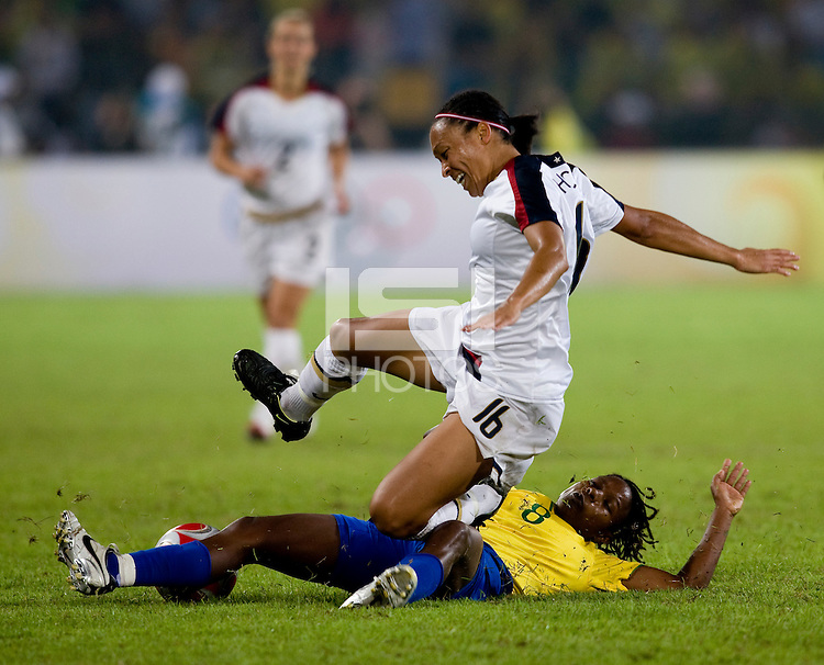 USWNT midfielder (16) Angela Hucles is tackled by Brazilian midfielder (8) Formiga while playing for the gold medal at Workers' Stadium.  The USWNT defeated Brazil, 1-0, during the 2008 Beijing Olympic final in Beijing, China.