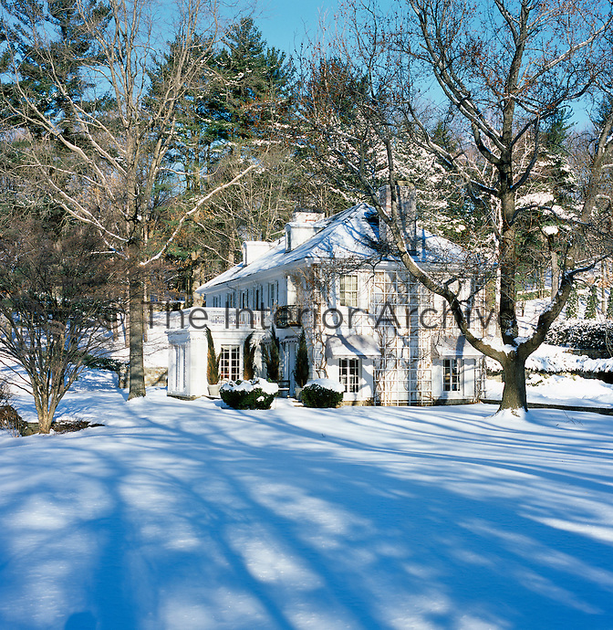 A view of the rear of the property in winter from across the snow-covered lawn