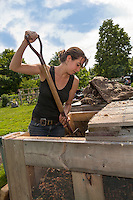 A young woman uses a garden fork to turn compost in a wooden three bin compost box system.