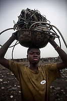 A boy carries electrical cables to a burning site at Agbogbloshie dump in order to retrieve copper, in Accra, Ghana.