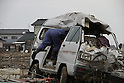 Just south of the Natori river the Yuriage area was made famous by the live NHK broadcast of the tsunami destroying its port and rolling over its fields while cars attempted to flee the deluge.  Masses of debris are pushed into piles which line roads and fields.  Here a local man recovers boxes of pipe fom this ruined van.