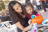 Tatiana Price and her daughter Katia, 2, decorate a pumpkin at the Main Street Farmers Market on Sunday, October 30, 2011.