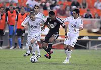 D.C. United midfielder Andy Najar (14) goes against Vancouver Whitecaps FC defender Jordan harvey (26) left and midfielder John Thorrington (11) right. D.C. United defeated The Vancouver Whitecaps FC 4-0 at RFK Stadium, Saturday August 13 , 2011.