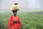 A woman walks in the foggy predawn in the Congolese village of Wembo Nyama..