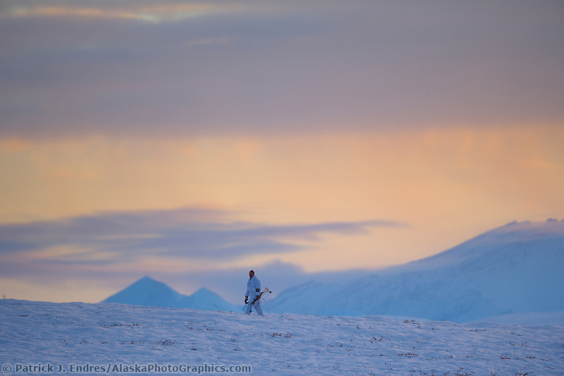 Bow hunter hikes a snow covered tundra ridge in the Brooks Range, Arctic, Alaska