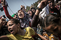 In this Friday, Jul. 05, 2013 photo, members of the Muslim Brotherhood and supporters of the ousted president Morsi shout slogans as they rally after praying at the University of Cairo in Giza district against the coup that has left many of its leaders in prison, Cairo, Egypt. (Photo/Narciso Contreras).