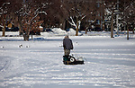 A ice fisherman dragging a sled across the ice  on Lake Monona Bay in Madison, Wisconsin.